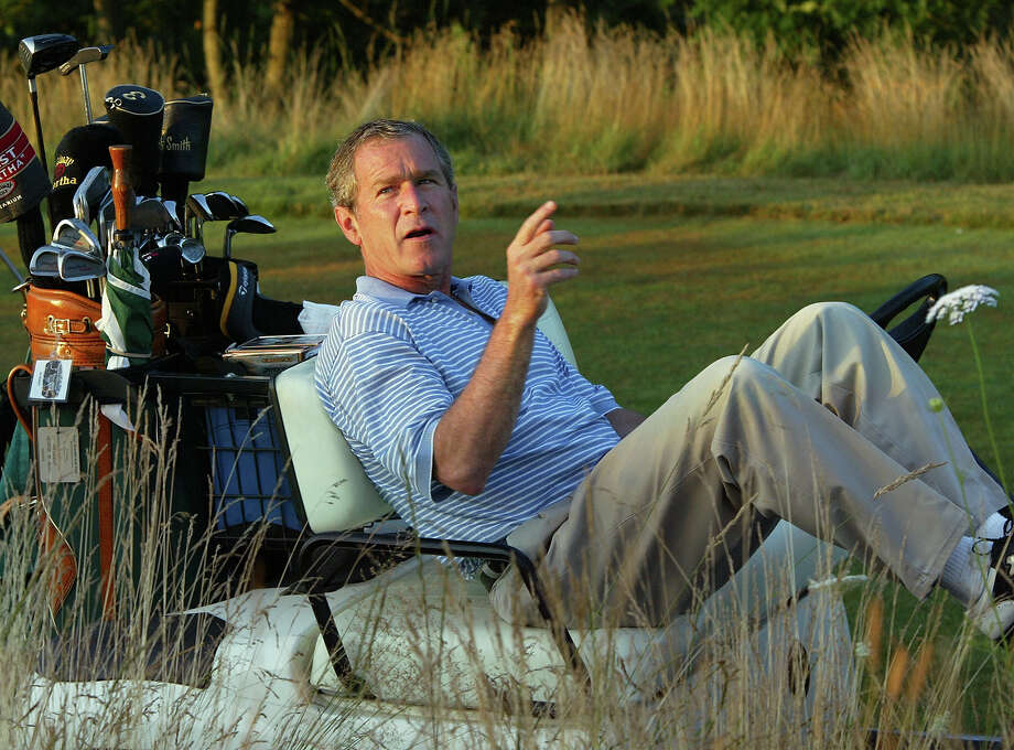 President Bush stretches out in his golf cart at the Cape Arundel Golf Club in Kennebunkport, Maine, Aug. 4, 2002. Bush was visiting his family and playing golf with his father, former President George H.W. Bush, before starting vacation at his Crawford, Texas, ranch. Photo: Associated Press / Associated Press