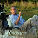 President Bush stretches out in his golf cart at the Cape Arundel Golf Club in Kennebunkport, Maine, Aug. 4, 2002. Bush was visiting his family and playing golf with his father, former President George H.W. Bush, before starting vacation at his Crawford, Texas, ranch.