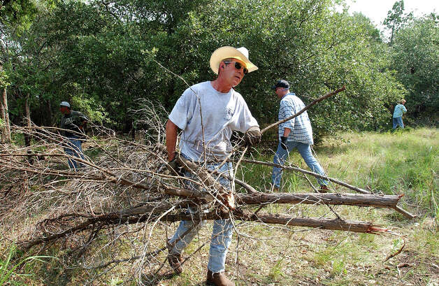 President Bush clears cedar at his 1,600-acre ranch in Crawford, Texas, Aug. 9, 2002. Photo: Associated Press / Associated Press