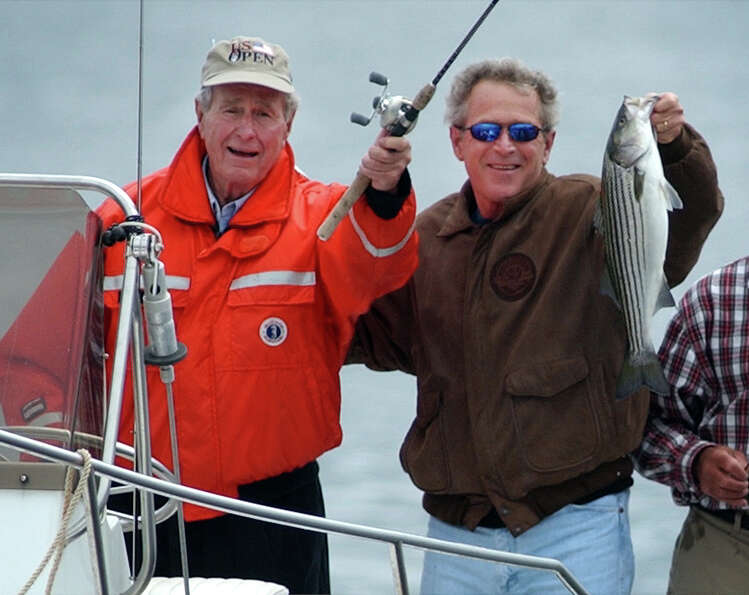 President Bush holds up a striped bass that he caught while fishing with his father, former Presiden
