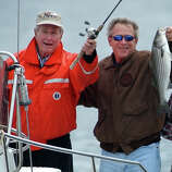 President Bush holds up a striped bass that he caught while fishing with his father, former President Bush, off the coast of Kennebunk, Maine, June 14, 2003.
