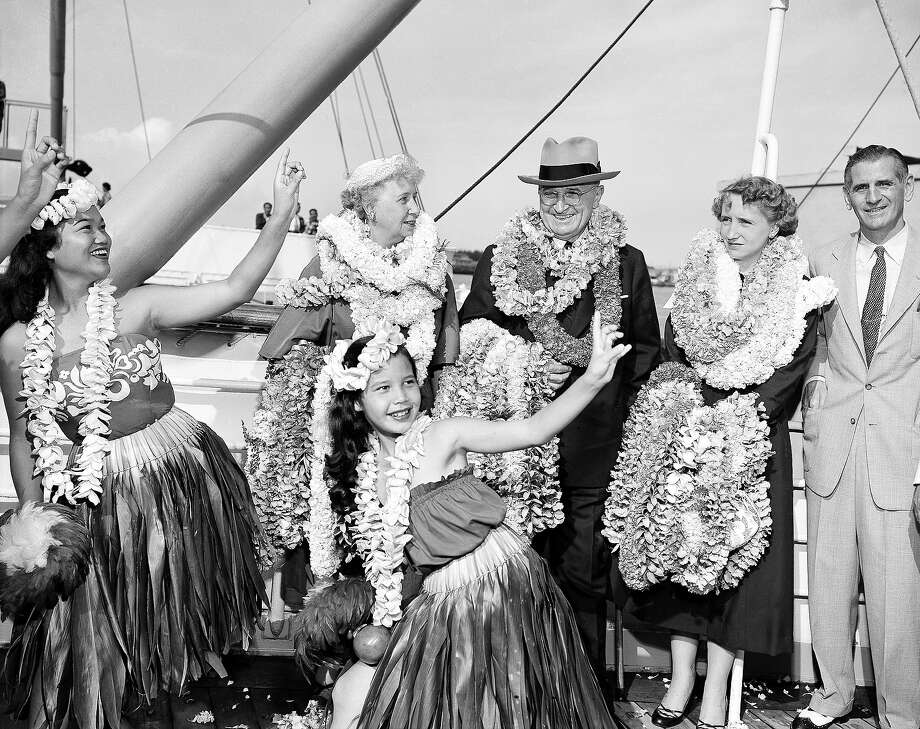 Former President Harry S Truman, his wife Bess and daughter Margaret Truman are bedecked with leis as a little Hawaiian girl entertains them on the deck of the liner President Cleveland at Honolulu, March 29, 1953. They took a month's vacation in Hawaii as guests of Ed Pauley, California oil man. Photo: Associated Press / Associated Press