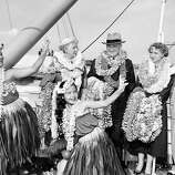 Former President Harry S Truman, his wife Bess and daughter Margaret Truman are bedecked with leis as a little Hawaiian girl entertains them on the deck of the liner President Cleveland at Honolulu, March 29, 1953. They took a month's vacation in Hawaii as guests of Ed Pauley, California oil man.