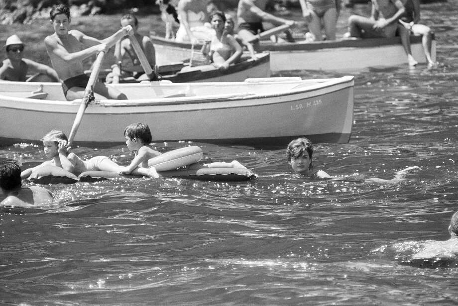 Mrs. Jacqueline Kennedy pushes a rubber mattress in which her 4-year-old daughter Caroline, left, and her nephew Anthony Radziwill, 2, were lying during a swim in the Mediterranean on Aug. 9, 1962. The first lady and her daughter spent a two-week vacation at Ravello, Italy. Photo: Associated Press / Associated Press