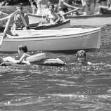 Mrs. Jacqueline Kennedy pushes a rubber mattress in which her 4-year-old daughter Caroline, left, and her nephew Anthony Radziwill, 2, were lying during a swim in the Mediterranean on Aug. 9, 1962. The first lady and her daughter spent a two-week vacation at Ravello, Italy.