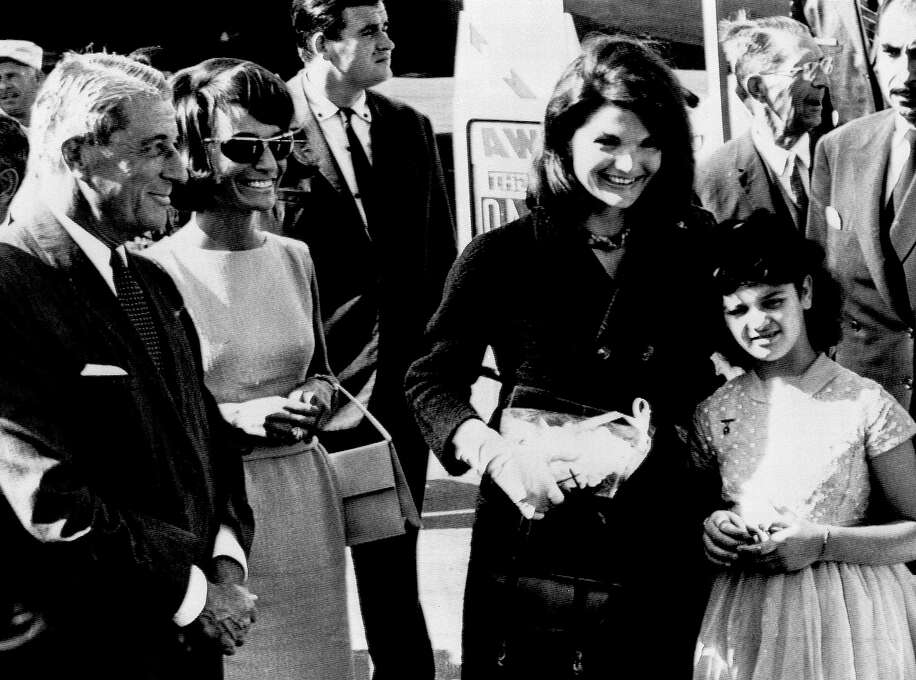 Memi Papacotsis, 12, stands with Mrs. Jacqueline Kennedy on the first lady's arrival at Athens airport on Oct. 2, 1963, for a vacation in Greece. The youngster was flown to Washington's Walter Reed Hospital from Greece for a heart operation in 1962 through the efforts of Mrs. Kennedy, who had met her on a previous visit to Greece. Also on hand to greet the president's wife was her sister, Princess Lee Radziwill, second from right, and U.S. Ambassador Henry Labouisse.  Photo: Associated Press / Associated Press