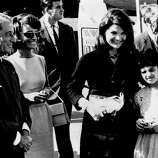 Memi Papacotsis, 12, stands with Mrs. Jacqueline Kennedy on the first lady's arrival at Athens airport on Oct. 2, 1963, for a vacation in Greece. The youngster was flown to Washington's Walter Reed Hospital from Greece for a heart operation in 1962 through the efforts of Mrs. Kennedy, who had met her on a previous visit to Greece. Also on hand to greet the president's wife was her sister, Princess Lee Radziwill, second from right, and U.S. Ambassador Henry Labouisse.