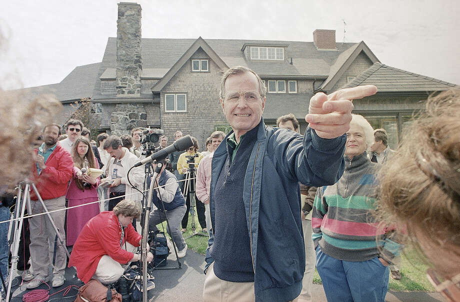 Vice President George Bush fields another question during a news conference in front of his Kennebunkport, Maine home, May 27, 1988, with his wife, Barbara, right, at his side. Bush, who was at his vacation retreat home for close to a week, said he wasn't bothered by polls that give Michael Dukakis a double-digit lead. Photo: Associated Press / Associated Press