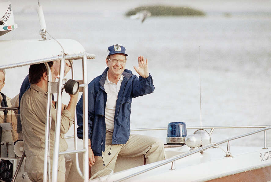 President-elect George H.  Bush waves to onlookers as his boat pulls away from the dock in Islamorad