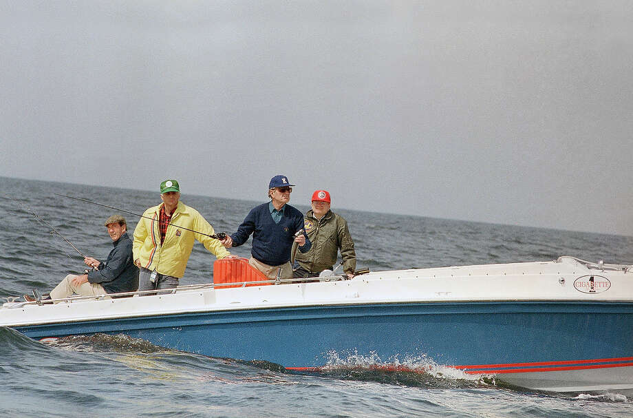 President George H. Bush, second from right, holds a fish in his hand as he points in a line from his boat during a fishing excursion in the waters near his vacation home in Kennebunkport, Maine, on May 20, 1989.    Others in the boat are unidentified. Photo: Associated Press / Associated Press