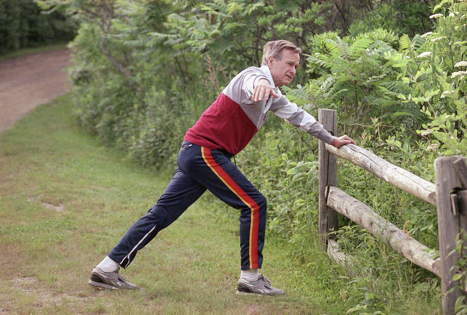 President George H. Bush stretches on a fence rail before jogging near his vacation home in Kennebunkport, Maine, July 1, 1989. Photo: Associated Press / Associated Press