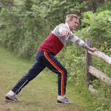 President George H. Bush stretches on a fence rail before jogging near his vacation home in Kennebunkport, Maine, July 1, 1989.