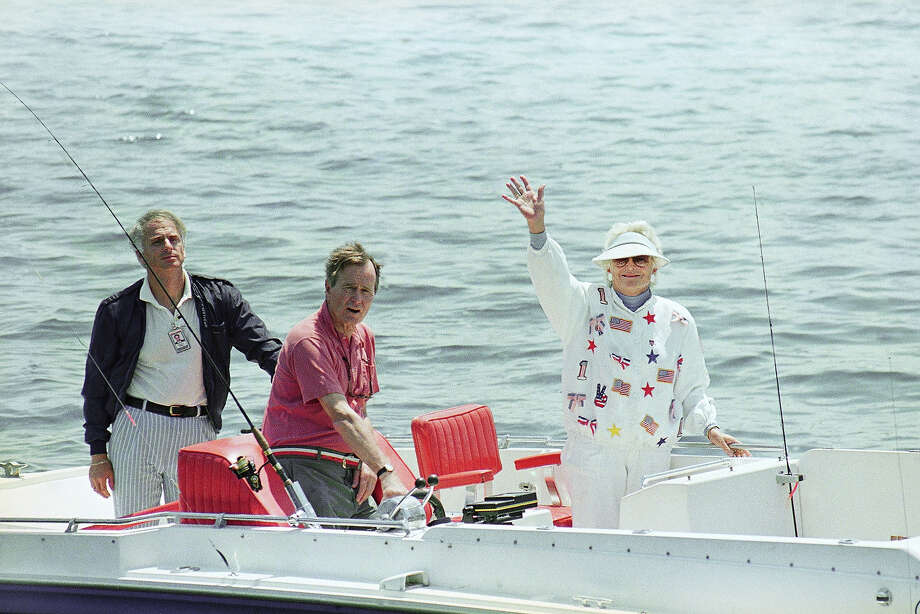 President George H. W. Bush, center, and first lady Barbara Bush, right, wave from their boat Fidelity while stopped at a local eatery, July 2, 1989, at Cape Porpoise, Maine. The Bushes were vacationing at their home on the Maine coast for the holiday weekend.  Photo: Associated Press / Associated Press
