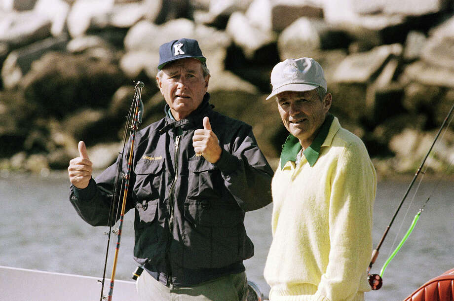 President George H. Bush gives a thumbs-up to photographers from his boat Fidelity while cruising the harbor in Wells, Maine, on Sept. 2, 1989.  The president spent Labor Day weekend at his vacation home in Kennebunkport, Maine.  Man at right is unidentified. Photo: Associated Press / Associated Press