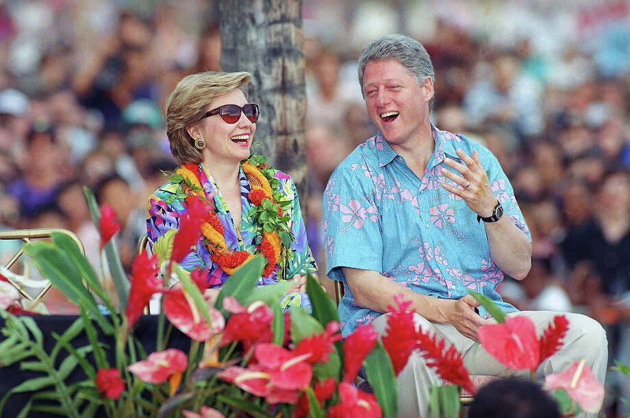 President Bill Clinton and his wife, first lady Hillary Rodham Clinton, smartly attired in Hawaii-style floral prints, share a hearty laugh at remarks before the introduction of the president on the beach at Waikiki, Honolulu, July 11, 1993. Some 20,000 came to hear Clinton speak on the first day of the first family's short vacation in Hawaii. Photo: Associated Press / Associated Press