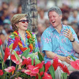 President Bill Clinton and his wife, first lady Hillary Rodham Clinton, smartly attired in Hawaii-style floral prints, share a hearty laugh at remarks before the introduction of the president on the beach at Waikiki, Honolulu, July 11, 1993. Some 20,000 came to hear Clinton speak on the first day of the first family's short vacation in Hawaii.