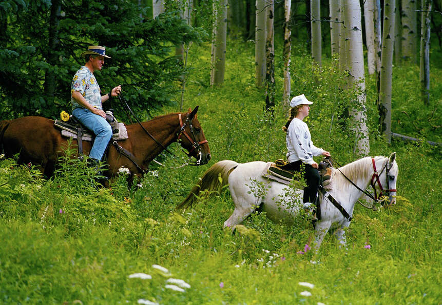 President Bill Clinton and daughter Chelsea take a horseback ride on Grouse Mountain in the resort t