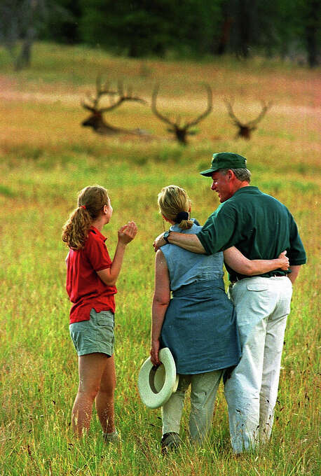 The first family share a laugh as they watch elk graze in a meadow in Yellowstone National Park in Wyoming on Aug. 12, 1996.  President Clinton, his wife Hillary and daughter Chelsea spent a day of their vacation hiking in Yellowstone. Photo: Associated Press / Associated Press
