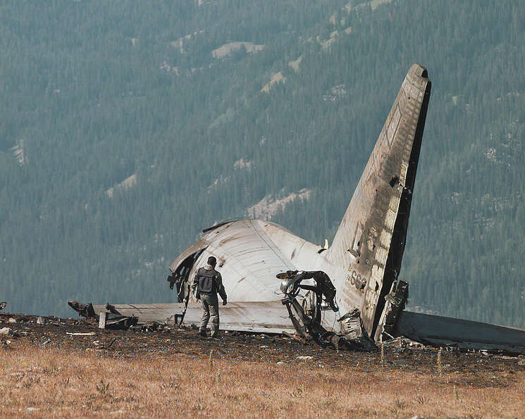 A member of an Air Force crash investigation team surveys on Aug. 20, 1996, the tail section of an A
