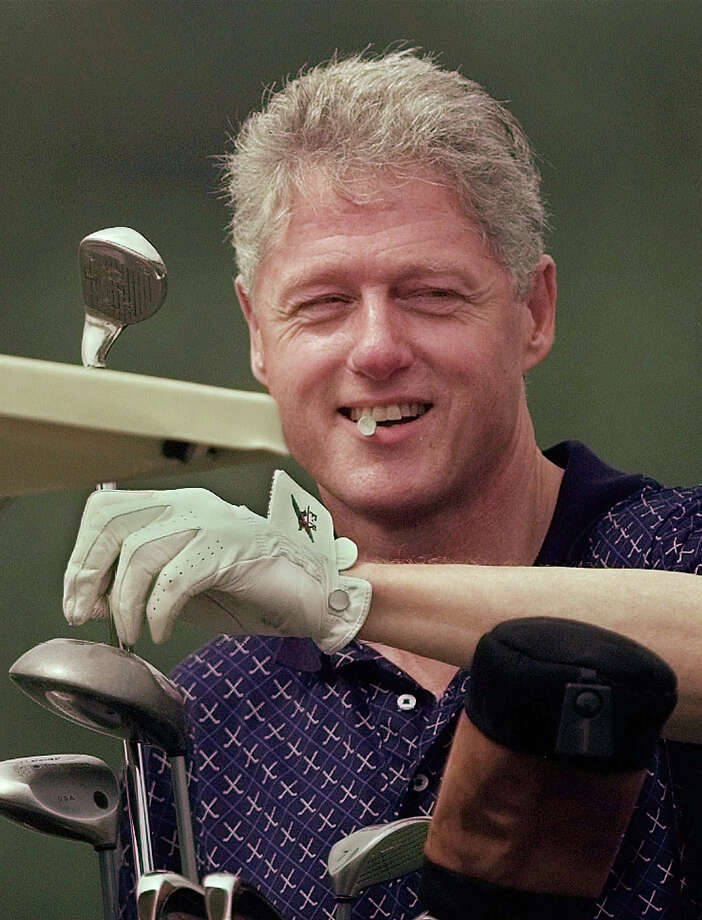 President Clinton holds a golf tee in his teeth while pulling a club from his bag during a round at Farm Neck Country Club in Oak Bluffs, Mass., Aug. 22, 1997. The president was wrapping up the first week of a three-week vacation on Martha's Vineyard in Cape Cod. Photo: Associated Press / Associated Press