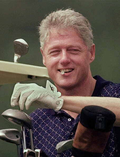 President Clinton holds a golf tee in his teeth while pulling a club from his bag during a round at