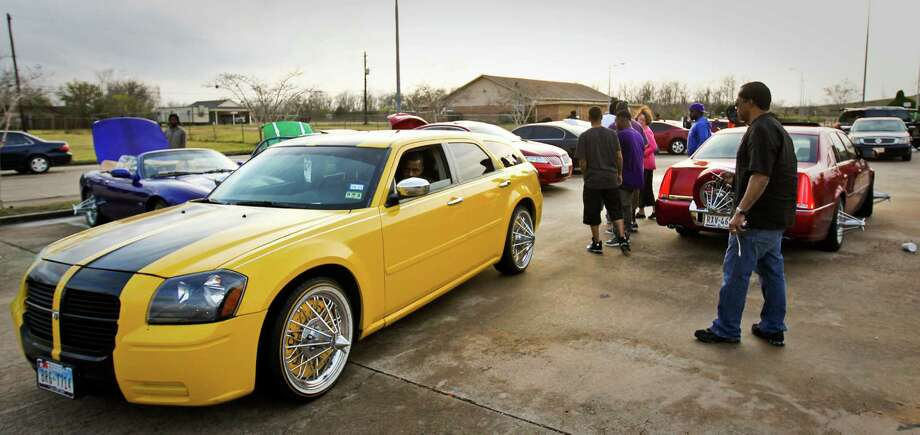 Yung Star drives his 'neat' yellow Dodge Magnum through a car get together, Wednesday, Dec. 19, 2012,  in Houston. His car describes as neat because he only has the custom paint, rims and wheels. Photo: Nick De La Torre, Houston Chronicle / © 2012  Houston Chronicle