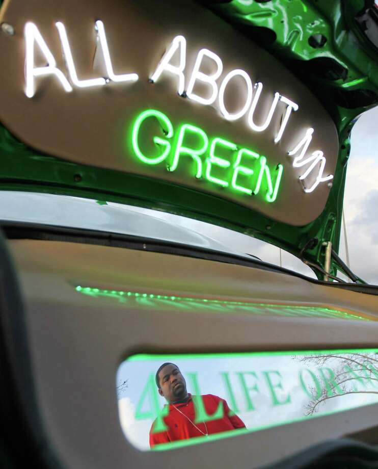 Marcus Bannis also known as M Beezy, , shows off his 'All About My Green' neon slab during a gathering of slab cars to be seen, Wednesday, Dec. 19, 2012,  in Houston. Bannis said he painted his vehicle green to represent his Fontaine neighborhood and his love of money. Photo: Nick De La Torre, Houston Chronicle / © 2012  Houston Chronicle