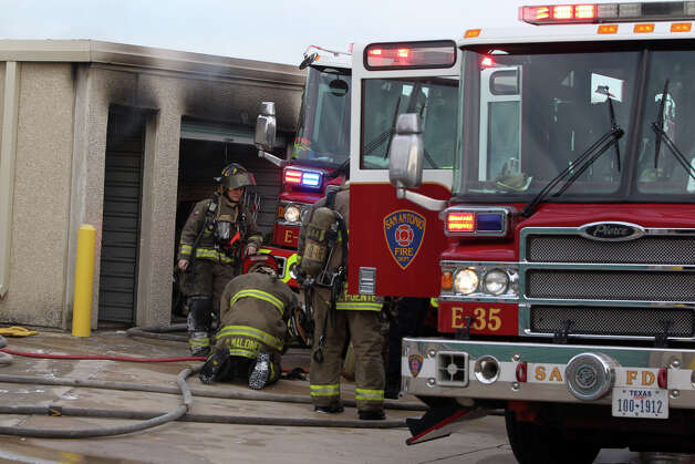 San Antonio firefighters work near burned storage units Monday January 7, 2013 after a fire started about 8:15 a.m. at Uncle Bob's Self Storage on the 7500 block of Culebra road. About 27 units at the facility were affected and the cause of the blaze is still being investigated. Photo: JOHN DAVENPORT, San Antonio Express-News / ©San Antonio Express-News/ Photo may be sold to the public