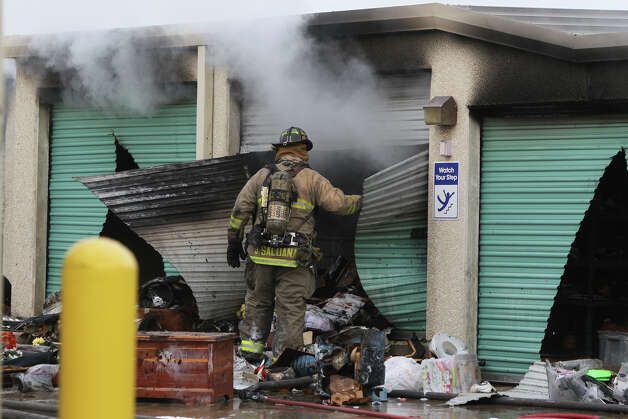 A San Antonio firefighter looks in a burned storage unit Monday January 7, 2013 after a fire started about 8:15 a.m. at Uncle Bob's Self Storage on the 7500 block of Culebra road. About 27 units at the facility were affected and the cause of the blaze is still being investigated. Photo: JOHN DAVENPORT, San Antonio Express-News / ©San Antonio Express-News/ Photo may be sold to the public