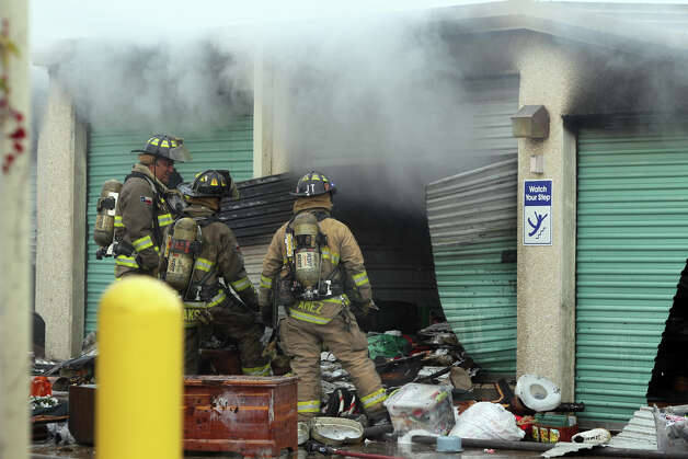 San Antonio firefighters look in a burned storage unit Monday January 7, 2013 after a fire started about 8:15 a.m. at Uncle Bob's Self Storage on the 7500 block of Culebra road. About 27 units at the facility were affected and the cause of the blaze is still being investigated. Photo: JOHN DAVENPORT, San Antonio Express-News / ©San Antonio Express-News/ Photo may be sold to the public