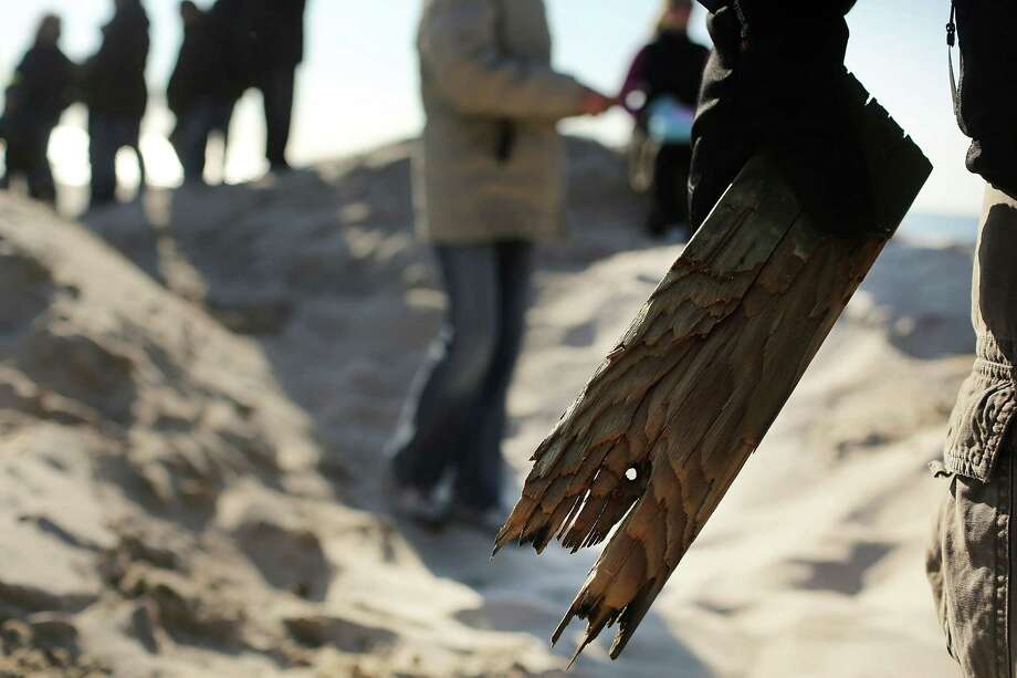 "LONG BEACH, NY - JANUARY 05: A man holds a piece of the Long Beach boardwalk as hundreds of residents of Long Beach, Long Island attend a ""goodbye"" ceremony for the town's historic wooden boardwalk, which was badly damaged in Hurricane Sandy, on January 5, 2013 in Long Beach, New York. Residents were given a final opportunity to say goodbye to the landmark boardwalk and to take a piece home before it was to be demolished and eventually replaced with a new boardwalk. The demolition is expected to take about a month. Photo: Spencer Platt, Getty Images / 2013 Getty Images"