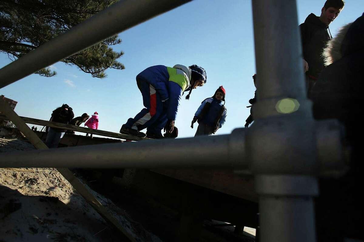 LONG BEACH, NY - JANUARY 05: Hundreds of residents of Long Beach, Long Island climb onto the boardwalk during a