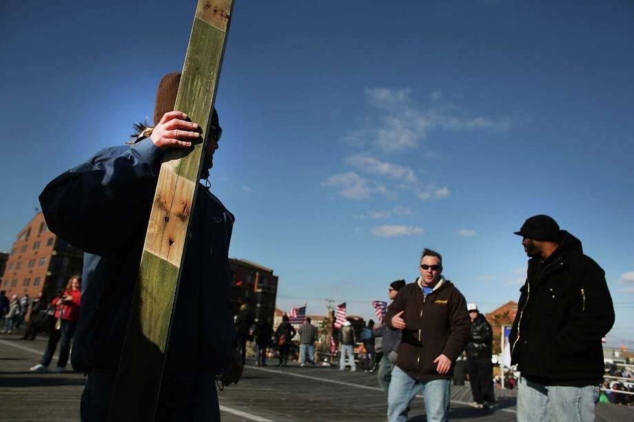 "LONG BEACH, NY - JANUARY 05:  Hundreds of residents of Long Beach, Long Island climb onto the boardwalk during a ""goodbye"" ceremony for the town's historic wooden boardwalk, which was badly damaged in Hurricane Sandy, on January 5, 2013 in Long Beach, New York. Residents were given a final opportunity to say goodbye to the landmark boardwalk and to take a piece home before it was to be demolished and eventually replaced with a new boardwalk. The demolition is expected to take about a month. Photo: Spencer Platt, Getty Images / 2013 Getty Images"