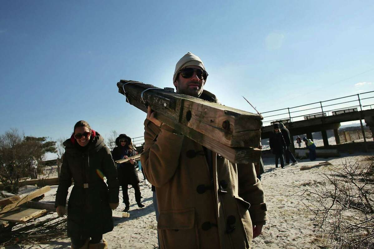 LONG BEACH, NY - JANUARY 05: Harris Rappel walks away with a piece of the Long Beach boardwalk as hundreds of residents of Long Beach, Long Island attend a