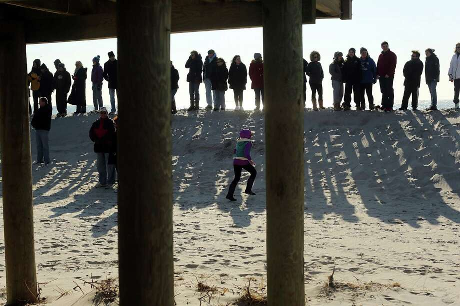 "LONG BEACH, NY - JANUARY 05:  Hundreds of residents of Long Beach, Long Island attend a ""goodbye"" ceremony for the town's historic wooden boardwalk, which was badly damaged in Hurricane Sandy, on January 5, 2013 in Long Beach, New York. Residents were given a final opportunity to say goodbye to the landmark boardwalk and to take a piece home before it was to be demolished and eventually replaced with a new boardwalk. The demolition is expected to take about a month. Photo: Spencer Platt, Getty Images / 2013 Getty Images"