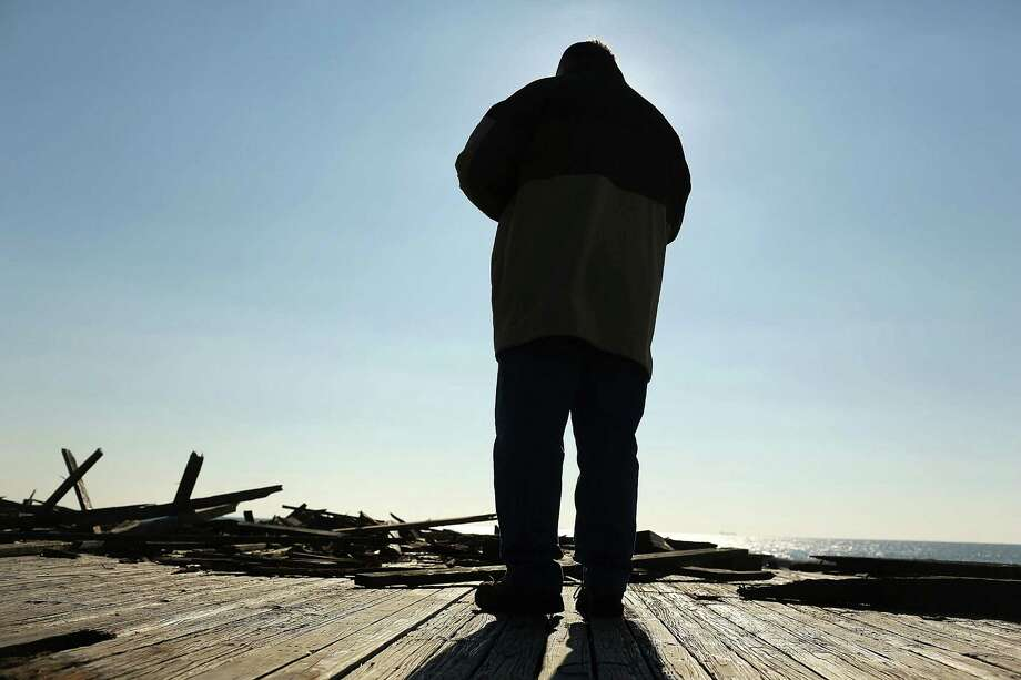 "LONG BEACH, NY - JANUARY 05:  A man stands before the remains of the Long Beach boardwalk as hundreds of residents of Long Beach, Long Island attend a ""goodbye"" ceremony for the town's historic wooden boardwalk, which was badly damaged in Hurricane Sandy, on January 5, 2013 in Long Beach, New York. Residents were given a final opportunity to say goodbye to the landmark boardwalk and to take a piece home before it was to be demolished and eventually replaced with a new boardwalk. The demolition is expected to take about a month. Photo: Spencer Platt, Getty Images / 2013 Getty Images"
