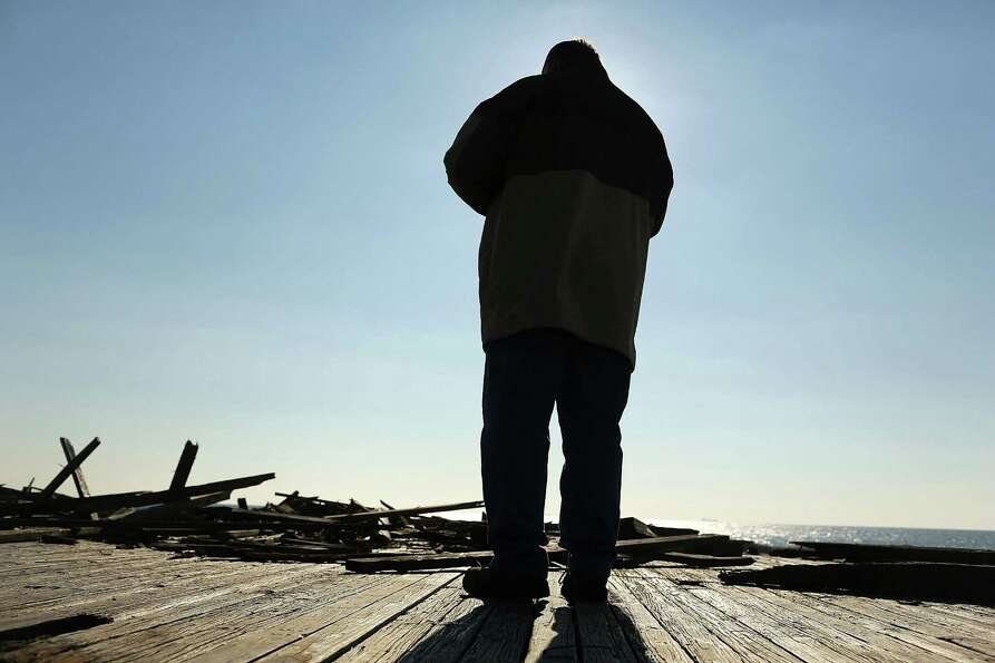 LONG BEACH, NY - JANUARY 05:  A man stands before the remains of the Long Beach boardwalk as hundred