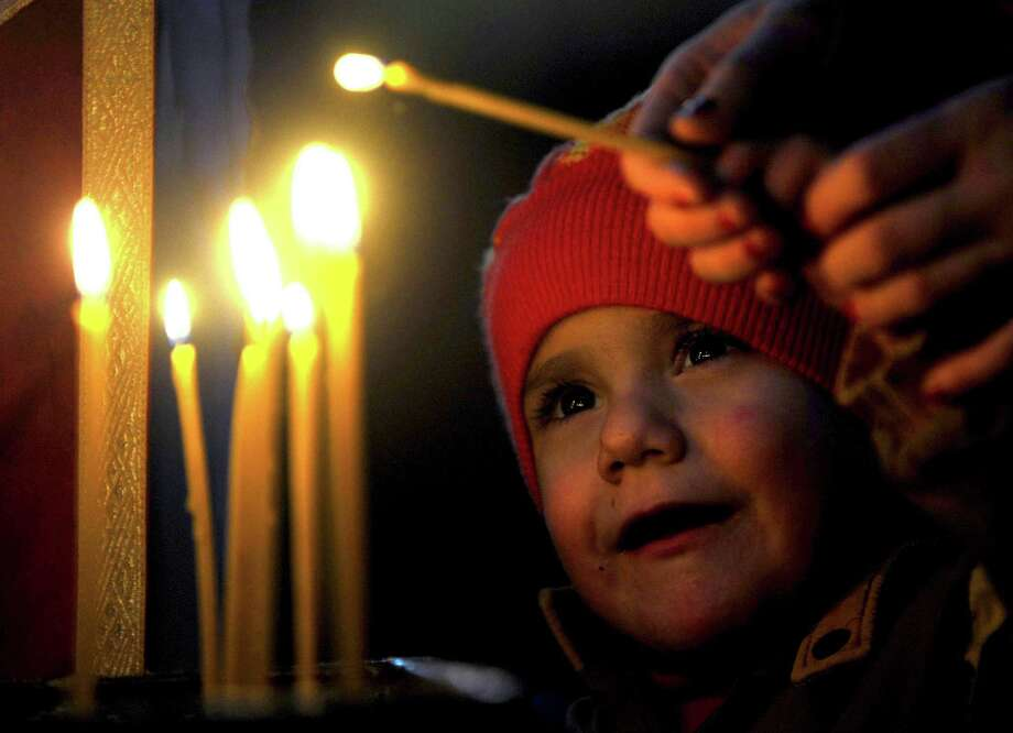 A boy lights a candle, during a Christmas service in the Christian Orthodox church,  St. Atanasij the Great, in the southeastern Macedonia's town of Bogdanci, on Monday, Jan. 7, 2013. Orthodox Christians celebrate Christmas day on January 7 because they follow the Julian Calendar, which was replaced in Western Europe by the Gregorian calendar 500 years ago. Photo: BORIS GRDANOSKI, AP / AP