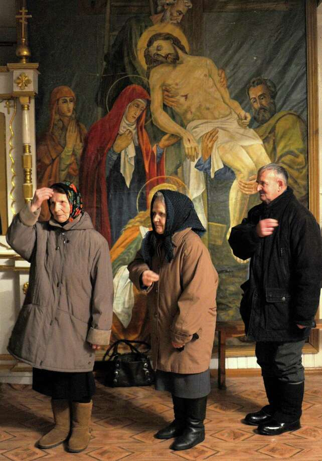 People attend a Christmas service in the town of Narovlia, some 330 km south-east of Minsk on January 6, 2013. Orthodox Christians celebrate Christmas on January 7 in the Middle East, Russia and other Orthodox churches that use the old Julian calendar instead of the 17th-century Gregorian calendar adopted by Catholics, Protestants, Greek Orthodox and commonly used in secular life around the world.     TOPSHOTS/AFP PHOTO/VIKTOR DRACHEVVIKTOR DRACHEV/AFP/Getty Images Photo: VIKTOR DRACHEV, AFP/Getty Images / AFP ImageForum