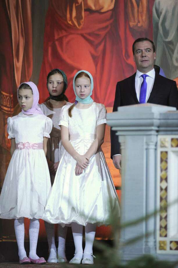 Russian Prime Minister Dmitry Medvedev (R) attends a Christmas service at the cathedral of Christ of Savior, in Moscow, early on January 7, 2013. Orthodox Christians celebrate Christmas on January 7 in the Middle East, Russia and other Orthodox churches that use the old Julian calendar instead of the 17th-century Gregorian calendar adopted by Catholics, Protestants, Greek Orthodox and commonly used in secular life around the world. AFP PHOTO / ALEXANDER NEMENOVALEXANDER NEMENOV/AFP/Getty Images Photo: ALEXANDER NEMENOV, AFP/Getty Images / AFP
