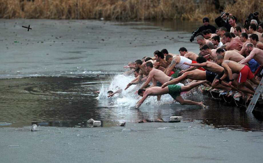 TOPSHOTS Bulgarians dive into a frozen lake to catch a cross in Sofia as part of Epiphany Day celebrations on January 6, 2013. It is believed that the first man to grab the cross, thrown into the water by an Eastern Orthodox priest, will be healthy throughout the year. AFP PHOTO / NIKOLAY DOYCHINOVNIKOLAY DOYCHINOV/AFP/Getty Images Photo: NIKOLAY DOYCHINOV, AFP/Getty Images / AFP