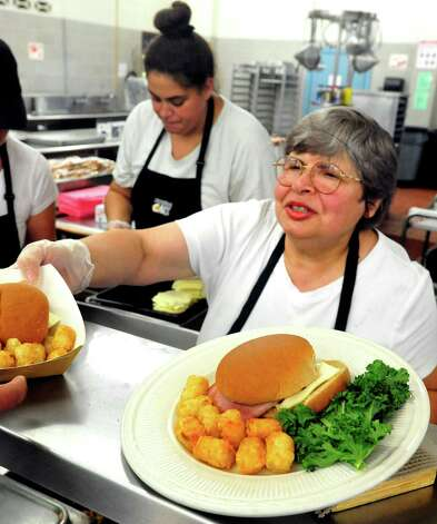Cafeteria worker Nadia Chaber serves a baked ham and cheese plate at Danbury High School Thursday, Oct. 11, 2012. Photo: Michael Duffy / The News-Times