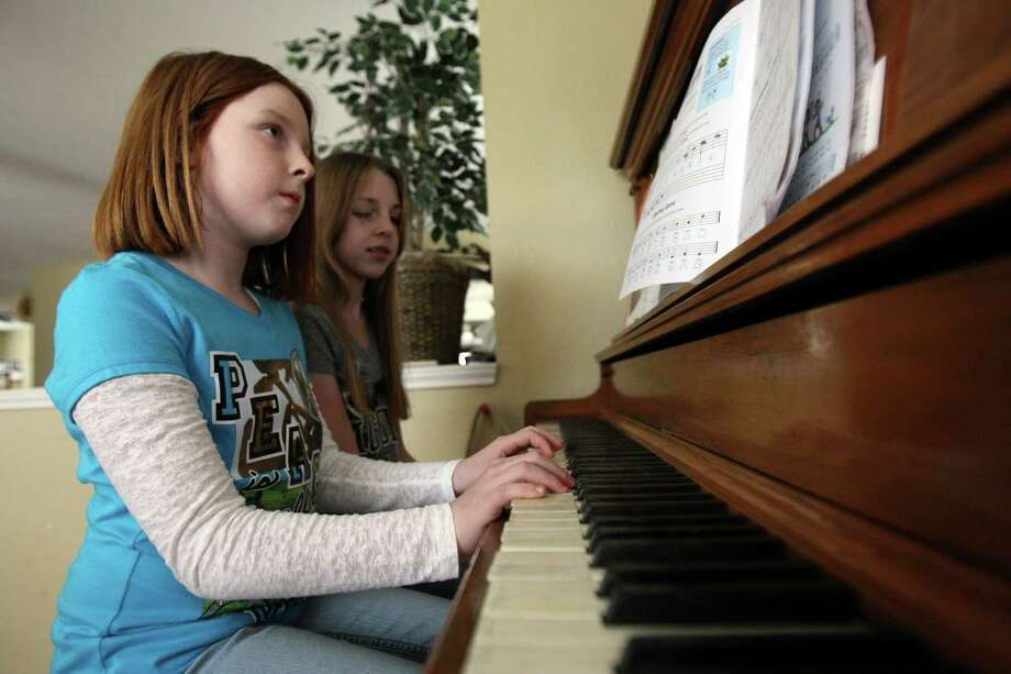 Tana Lux, 7, gets help with her piano lesson from her sister Tori, 12.  Their mom, Krista, says the girls will play piano until sixth grade, at which point they can choose whether to continue. Photo: Helen L. Montoya, San Antonio Express-News / ©SAN ANTONIO EXPRESS-NEWS
