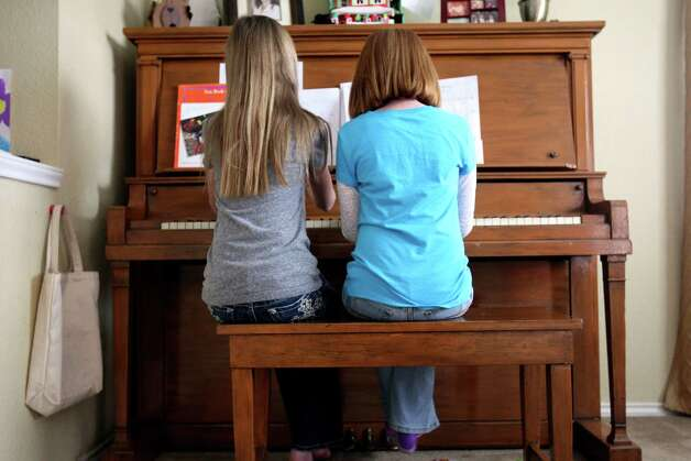 Tori Lux, 12 helps her sister Tana, 7, with her piano lesson on Thursday Jan. 3, 2013.  Their mom Krista is a fifth-grade teacher and encourages her girls to think about whether they still get joy from an activity but maintains a rule that if they want to quit, they have to wait till the end of the year or season. The one exception is piano -- because of research she has read on brain development, she set in stone that both girls will play piano until sixth grade, at which point they can choose whether to continue. Tori chose not to continue playing but is helping her sister learn to play. Photo: Helen L. Montoya, San Antonio Express-News / ©SAN ANTONIO EXPRESS-NEWS