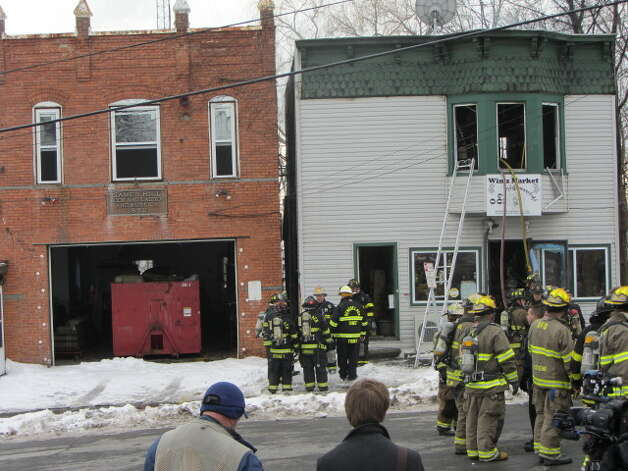 Firefighters battled a fire Monday morning at the Winn Market on Partition Street. Firefighters had to bolt from the 40 Partition St. building when flames weakened the structure and forced part of it to collapse. (BOB GARDINIER / TIMES UNION)