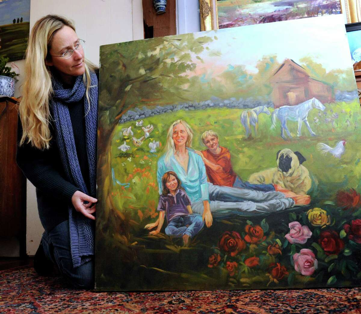 Scarlett Lewis, of Sandy Hook holds a painting that she did depicting herself with sons Jesse and JT on the family farm in Newtown, Thursday, Jan. 3, 2013.