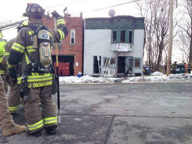 Firefighters battled a fire Monday morning at the Winn Market on Partition Street. Firefighters had to bolt from the 40 Partition St. building when flames weakened the structure and forced part of it to collapse. (Paul Buckowski/Times Union)
