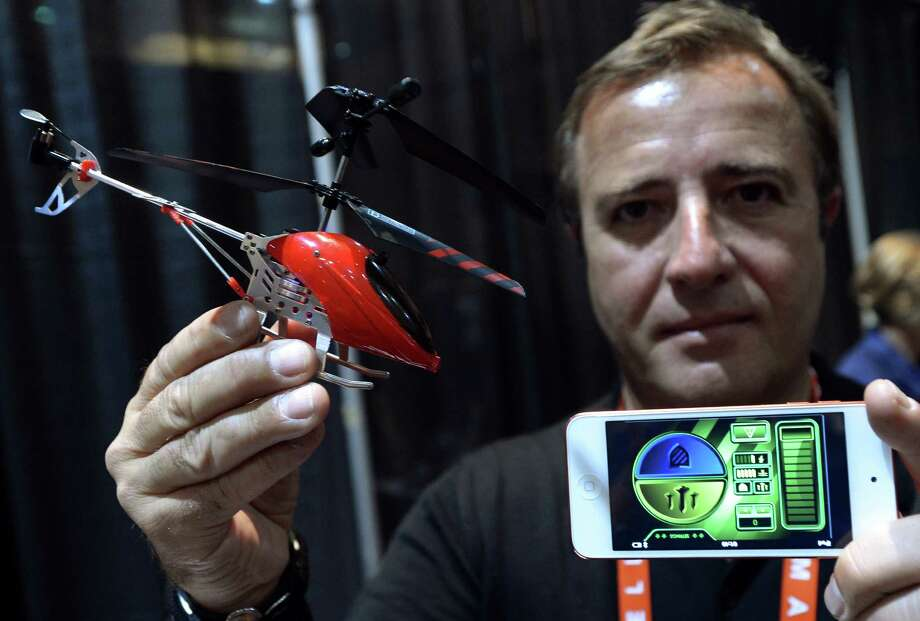 Thierry Dechatre of Avenir Telecom shows the BeWii bluetooth operated helicopter controlled by iPhone. Photo: JOE KLAMAR, AFP/Getty Images / AFP