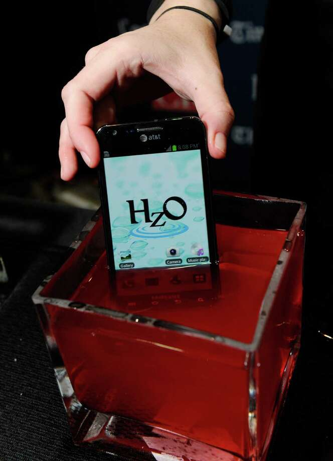 A smartphone using HzO Waterblock technology is displayed in a bowl of water. Photo: David Becker, Getty Images / 2013 Getty Images
