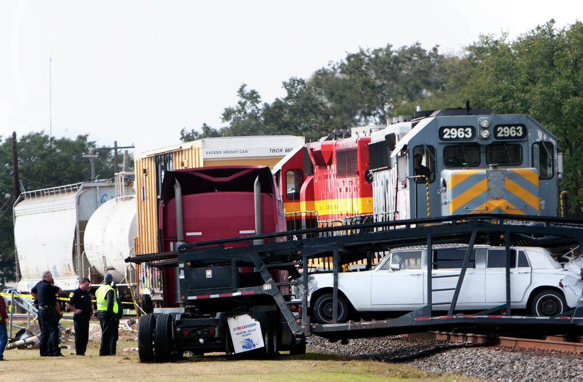 Investigators work the scene of a train accident on Brooks St. and U.S. 90, Monday, Jan. 7, 2013, in Sugarland. The driver of the truck was crossing the railroad tracks when its trailer got stuck on the tracks. The driver was not able to get off the tracks in time.